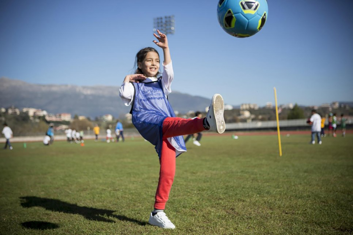 Young girl kicks ball during a refugee solidarity event.