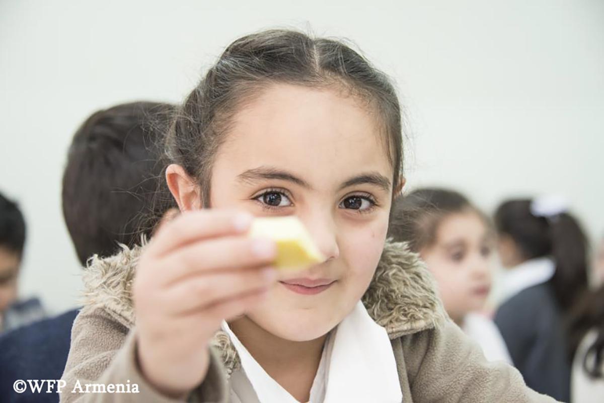 Աղջնակը ցույց է տալիս ձեռքի սնունդը և ժպտում
