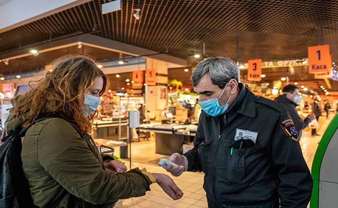 A security guard checks woman's fever with a remote thermometer.