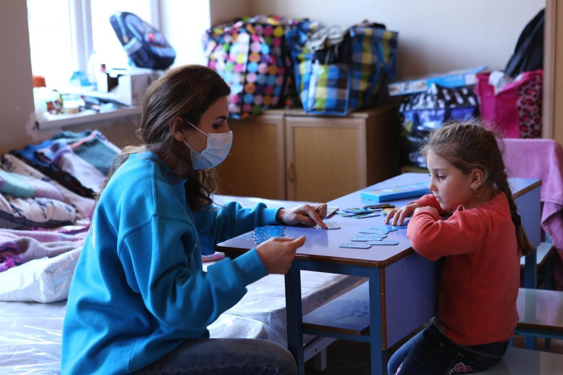 5-ամյա Լիան դոմինո է խաղում ՅՈՒՆԻՍԵՖ-ի աշխատակցի հետ ապաստարանում, որտեղ նա այժմ բնակվում է մայրիկի, քրոջ և տատիկի հետ: