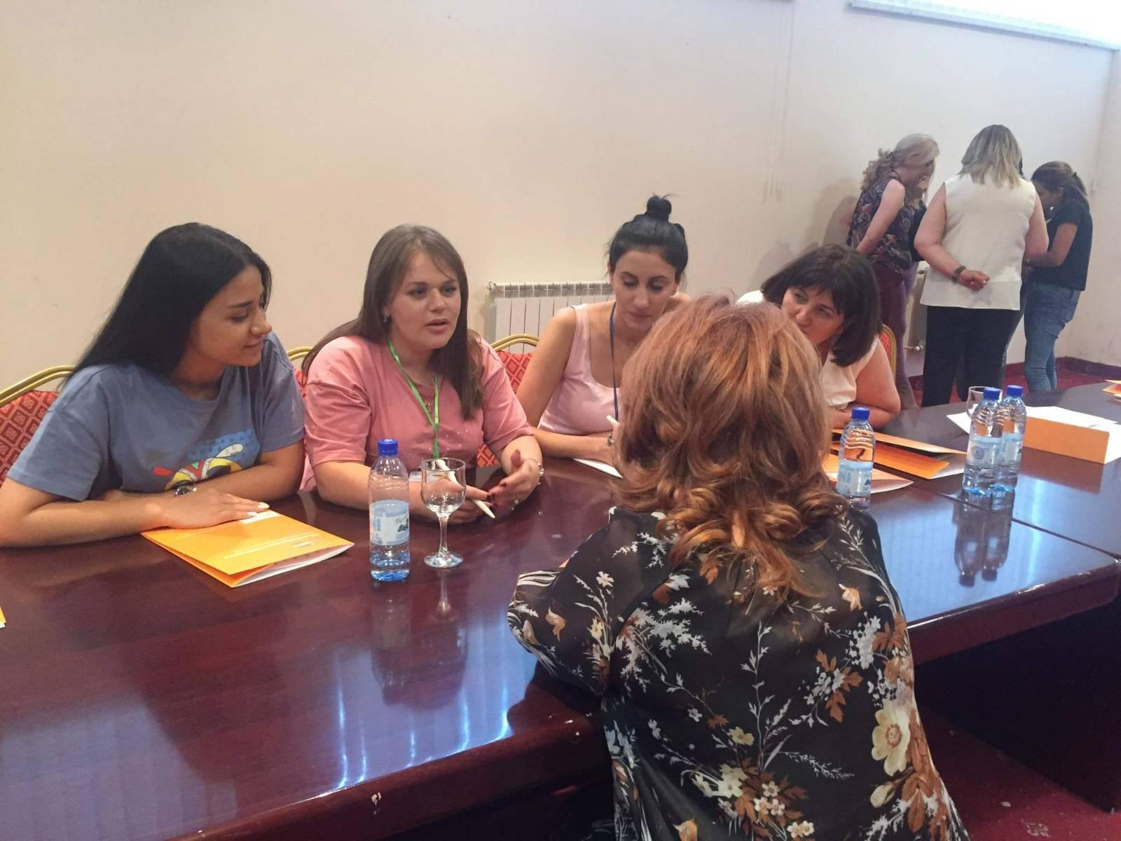 """A group of young women discuss a topic during the """"Caring without Hurting"""" EduCamp."""